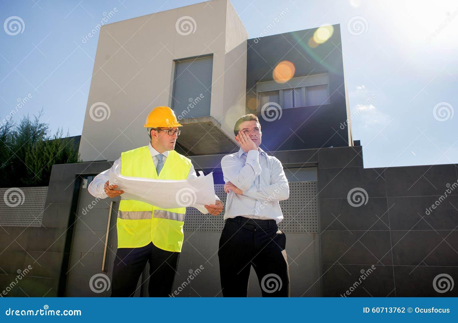 O cliente infeliz no esforço e no trabalhador do contramestre do construtor com capacete e a veste que discutem fora na construçã