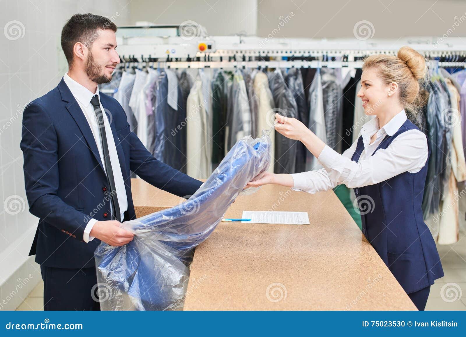 O cliente masculino toma a um trabalhador da lavanderia da mulher a roupa limpa