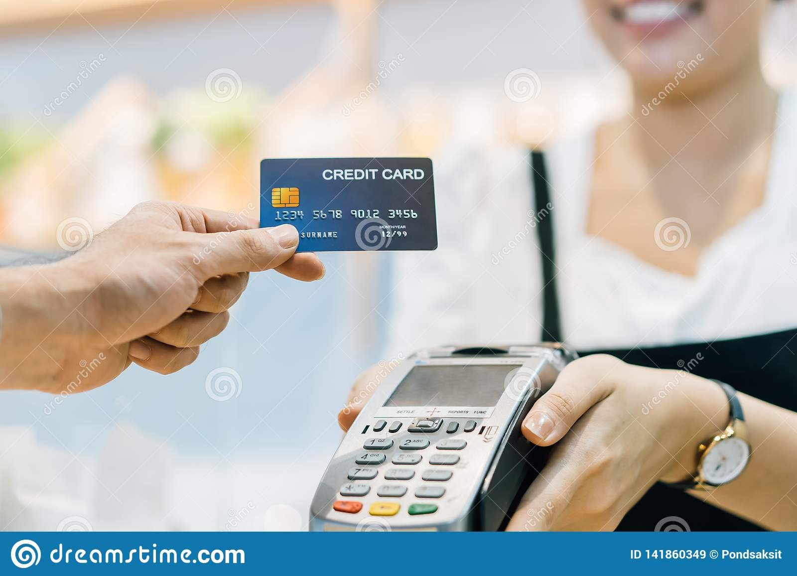 O cliente no café está pagando através do cartão de crédito ao assistente de loja