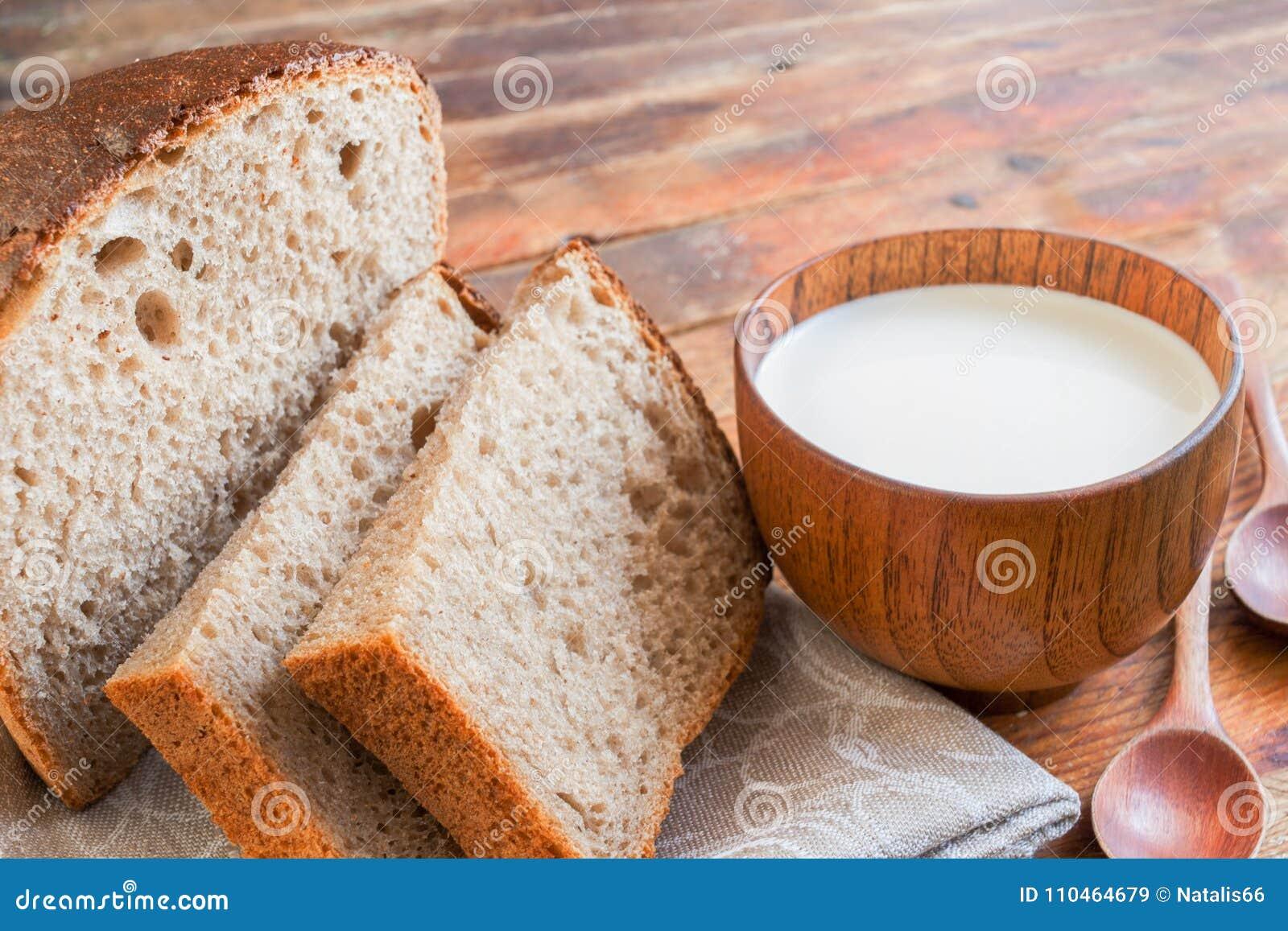 O close-up cortou o pão e um copo de madeira do leite em velho diagonal