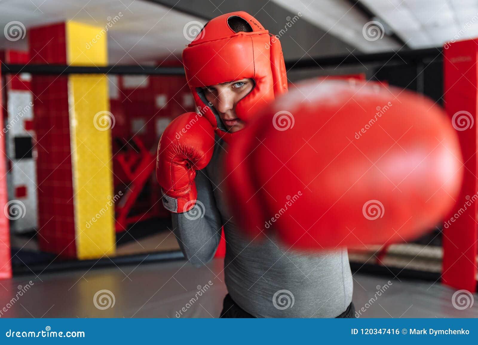 O close-up da luva de encaixotamento, o pugilista masculino contratou no treinamento no gym, em uma gaiola para uma luta sem regr