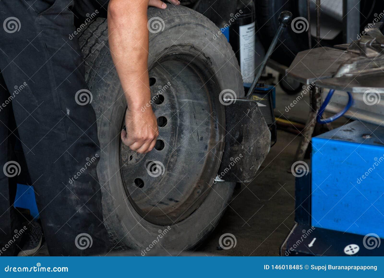 O close up da mudança do pneu, mecânico está mudando a roda de carro de equilíbrio do coordenador do pneu de carro no equilibrado