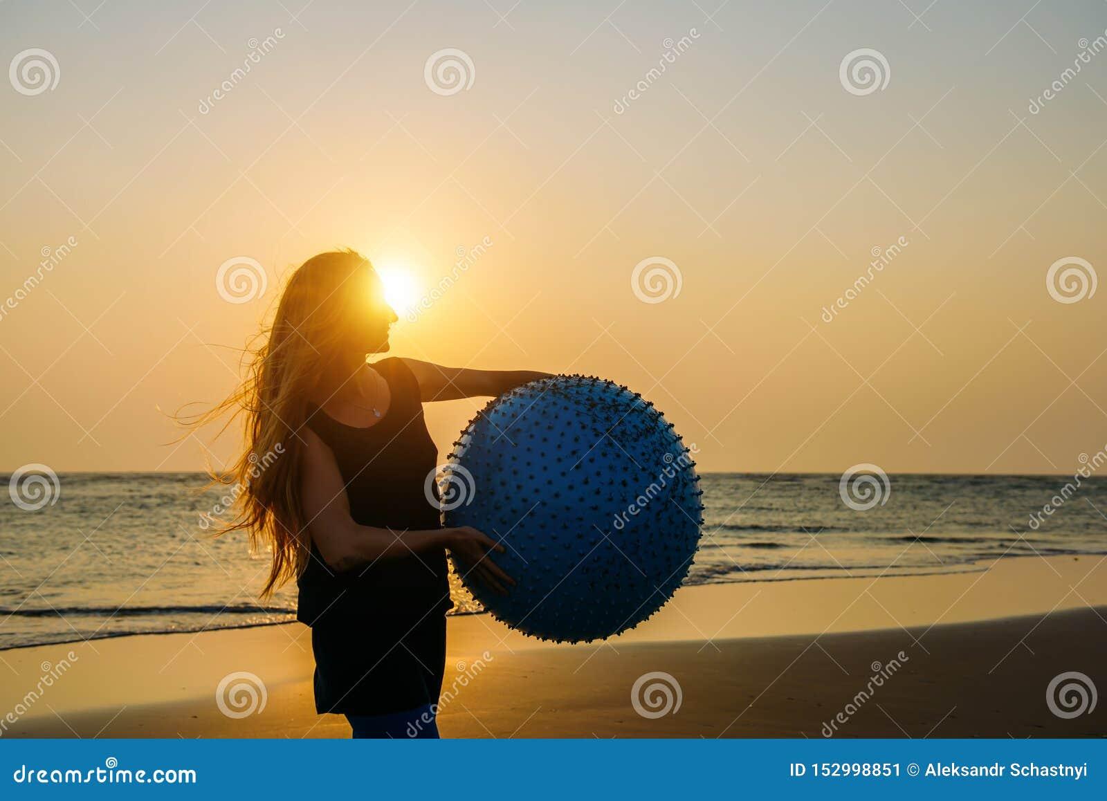 O close-up da mulher bonita nova com cabelo louro longo guarda a posição grande da bola da aptidão na praia à vista do sol de aju