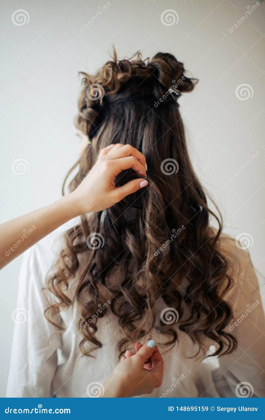 O close up das m?os f?meas do cabeleireiro ou do coiffeur faz o penteado