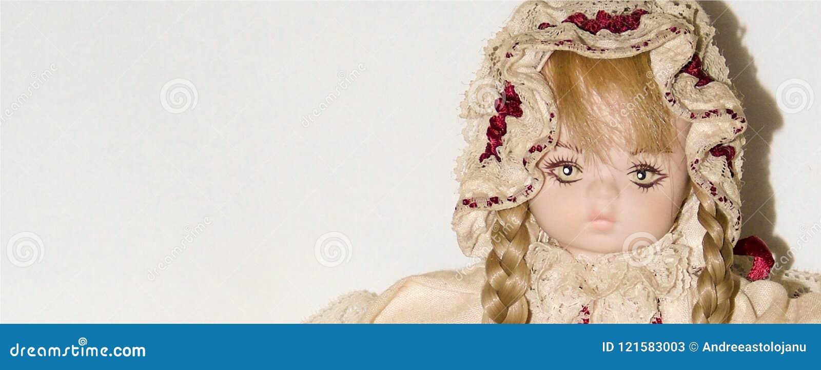 O close up de uma boneca loura da porcelana isolada no fundo branco, vintage brinca