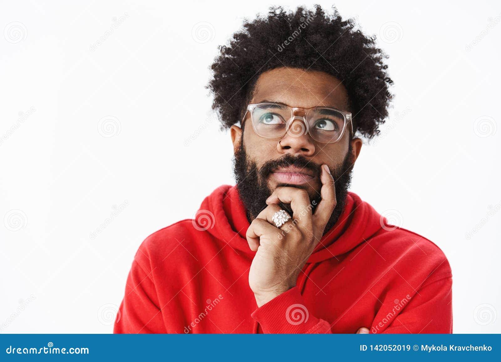 O close-up disparado da barba afro-americano pensativa da fricção do homem e de olhar o canto esquerdo superior focalizou, pensan