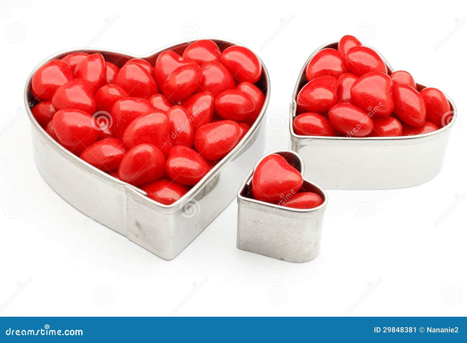 Latas dadas forma dos doces coração encarnado