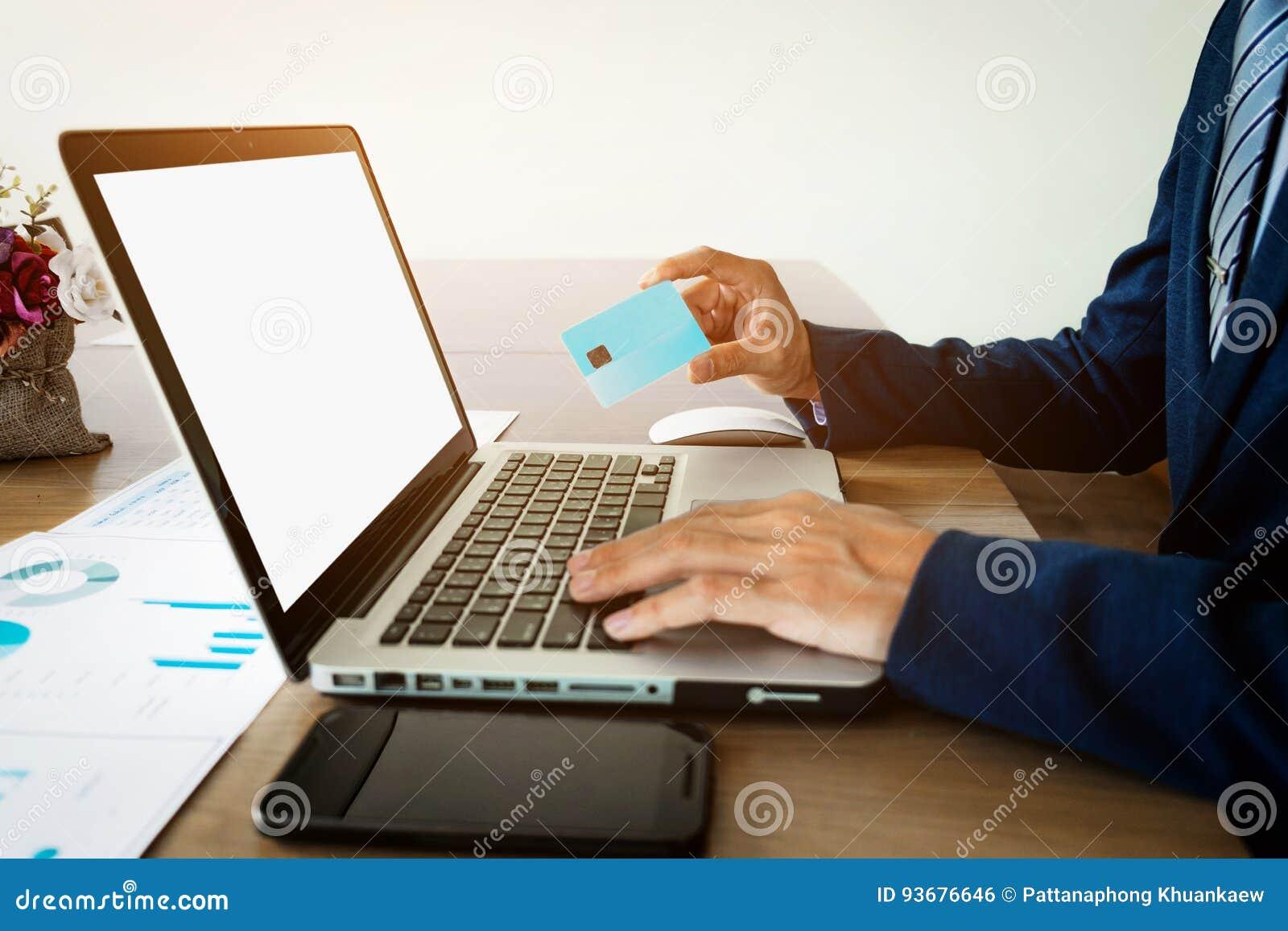 O close-up do homem entrega guardar o cartão, trabalhando no portátil a
