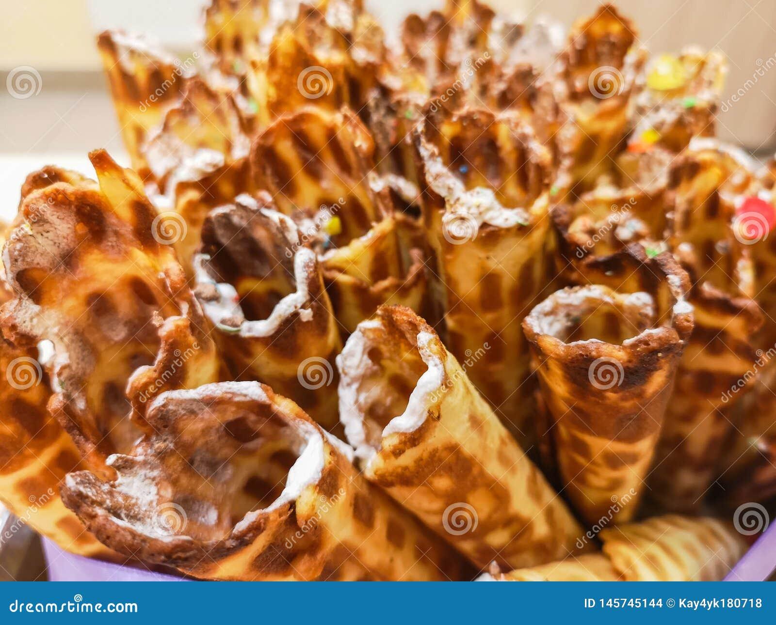 O close-up do waffle delicioso do chocolate rola a mentira na placa branca Prepara??o de uma sobremesa doce Cozinha e tabela limp