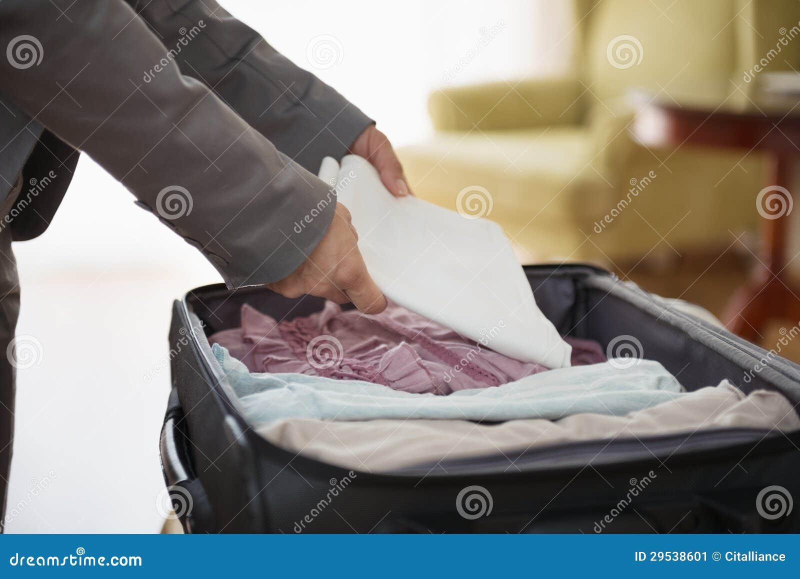 O close up na mulher de negócio desembala a bagagem no hotel