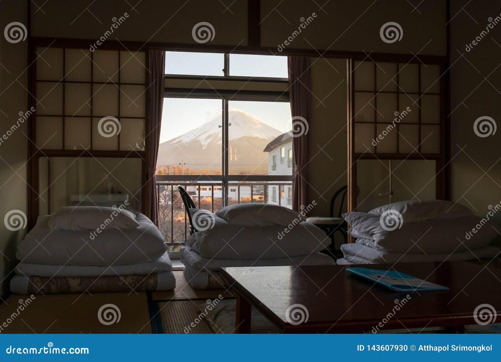 O colchão foi dobrado a pavimentar o sono em esteiras no estilo japonês e nas vistas de Monte Fuji na janela exterior
