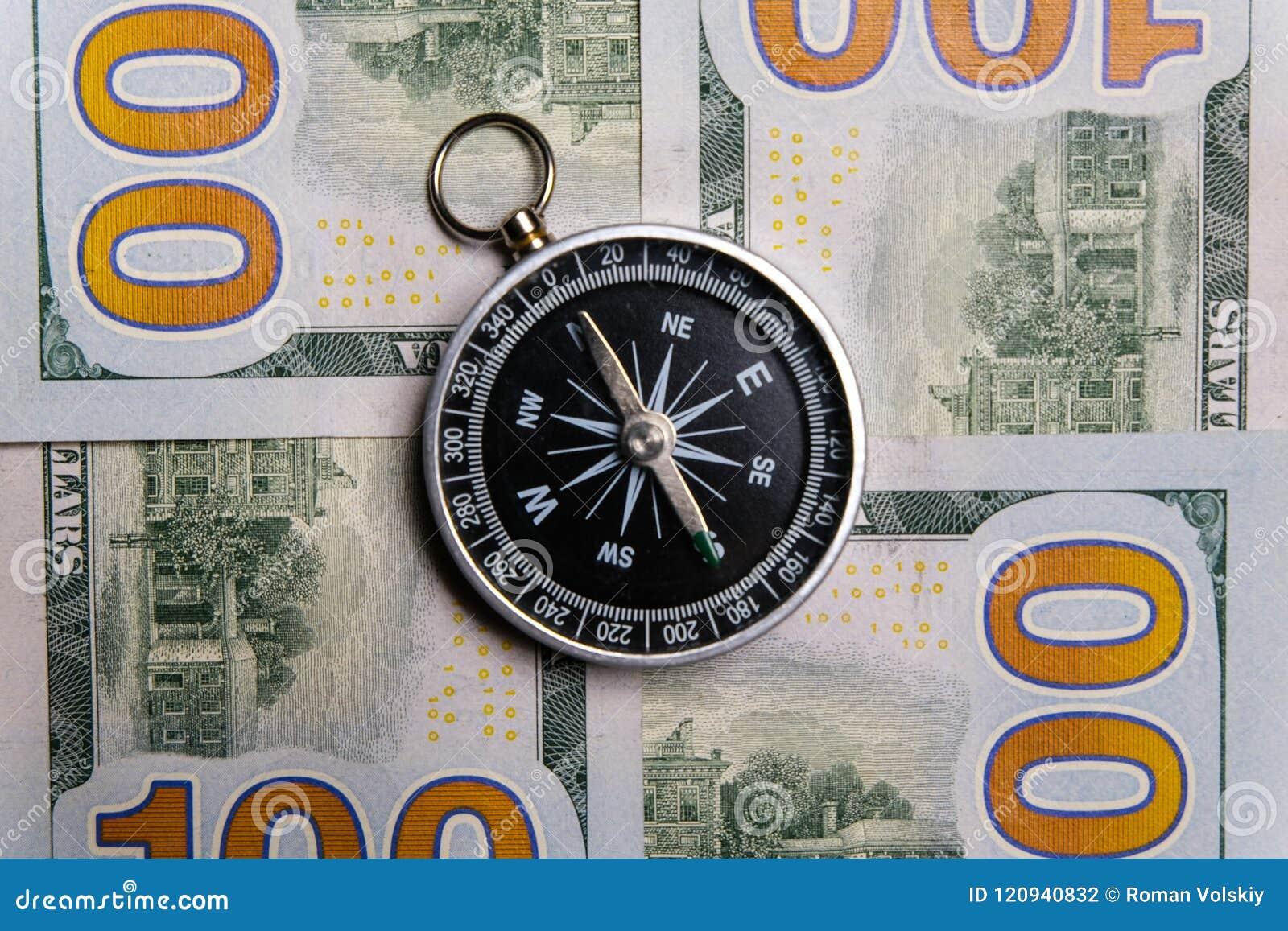 O compasso encontra-se em contas do dinheiro de cem-dólar Close-up