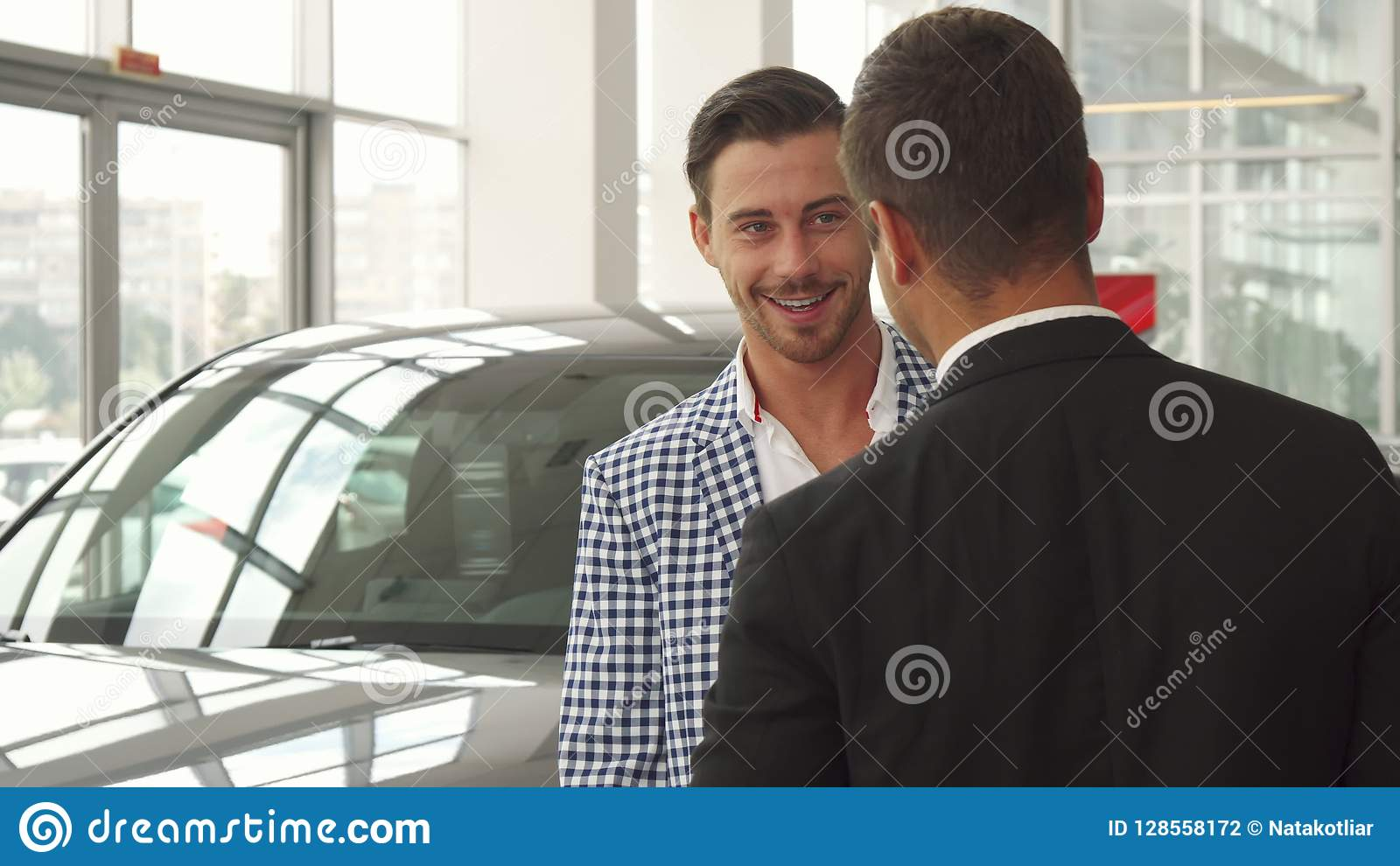 O comprador novo inspeciona o carro selecionado
