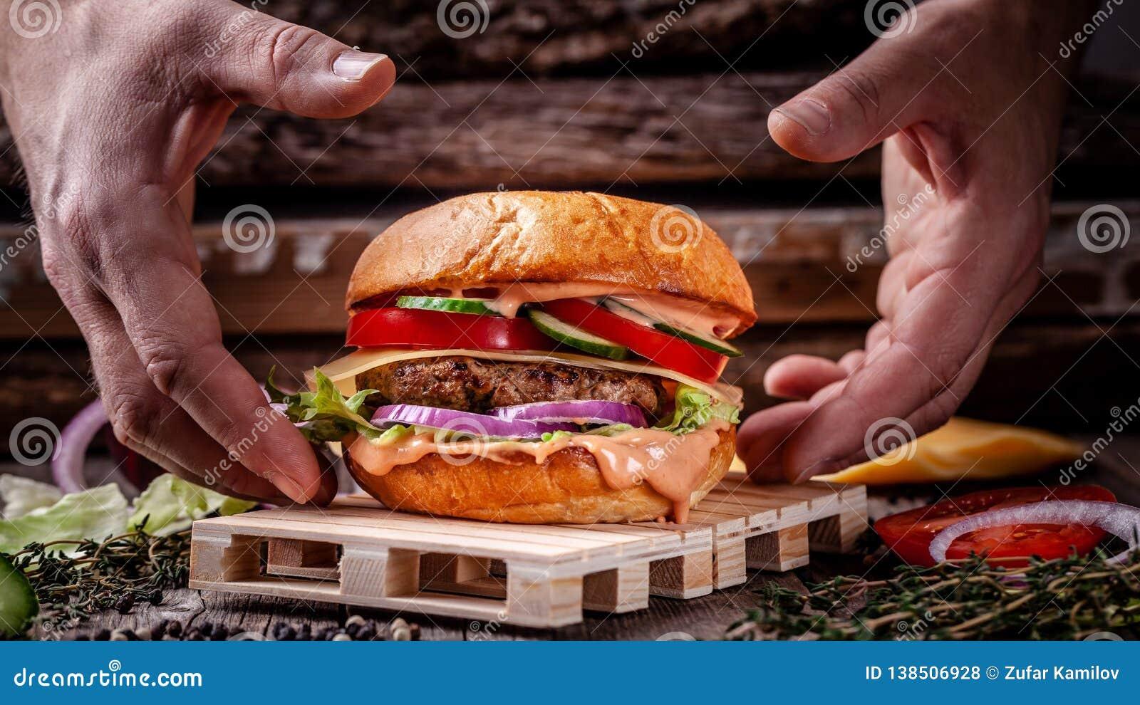 O conceito da culinária americana Hamburguer caseiro cozinhado por um homem de um bolo, de uma carne meaty e de umas costoletas d