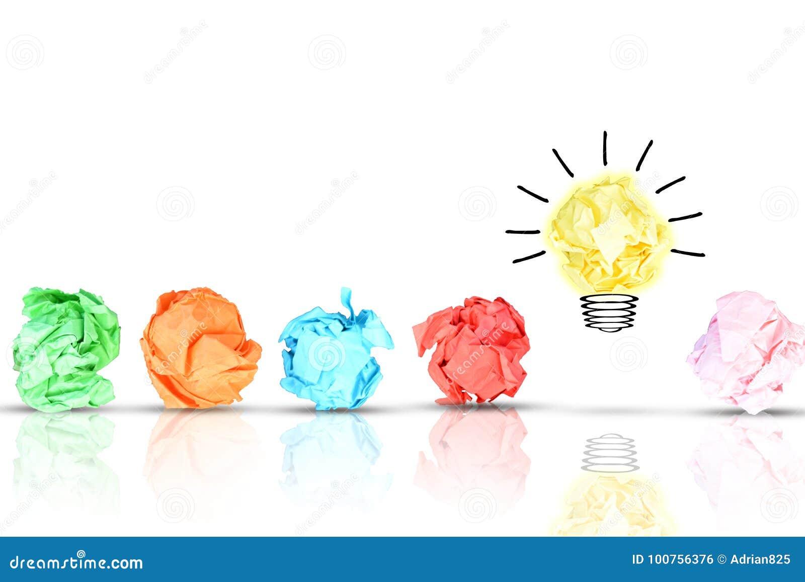 O conceito da descoberta com pedaços de papel amarrotados coloridos múltiplos em torno de uma ampola brilhante amarela deu forma