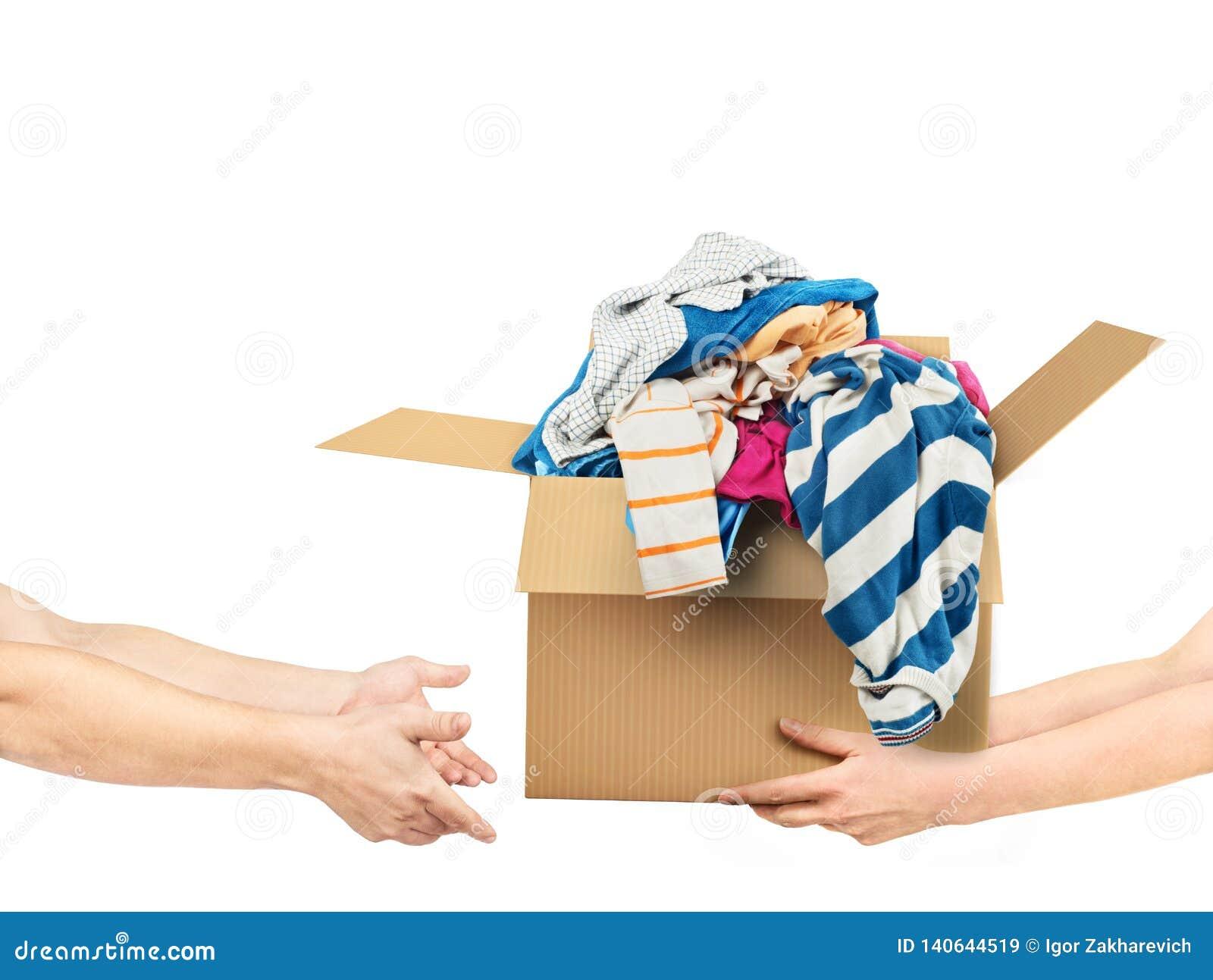 O conceito da doação As mãos estão dando uma caixa da roupa a outras mãos