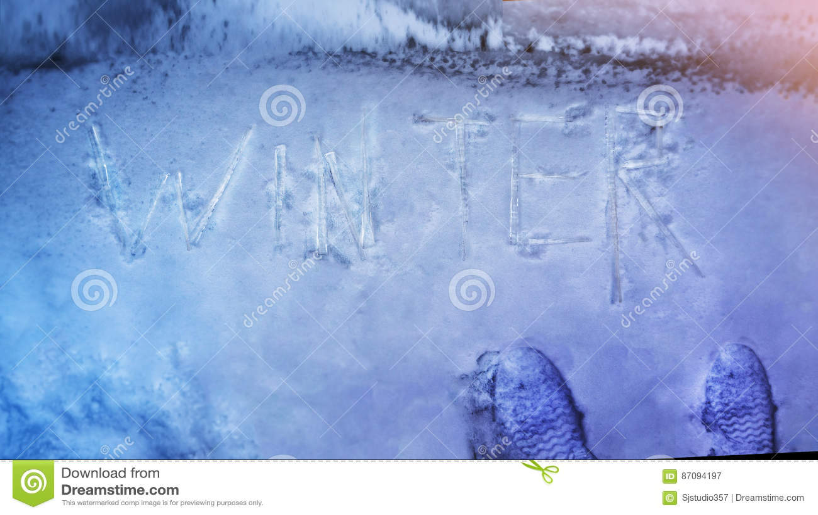 O conceito do inverno, escrito na neve por sincelos exprime o inverno, parte superior vi