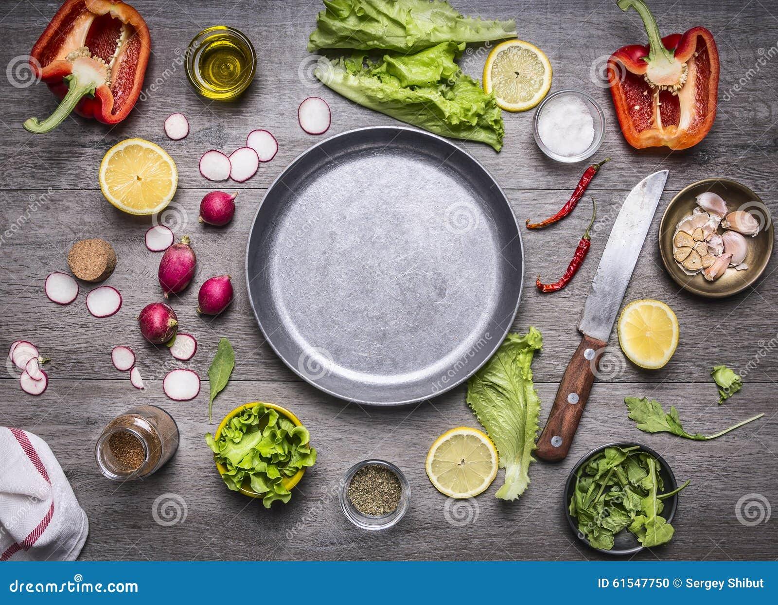 O conceito que cozinha os ingredientes de alimento do vegetariano apresentados em torno da bandeja com uma faca tempera o espaço