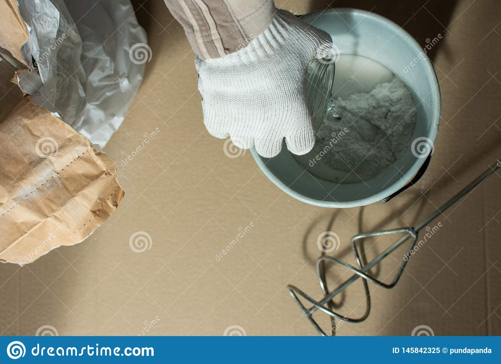 O construtor do homem prepara uma mistura para a massa de vidraceiro
