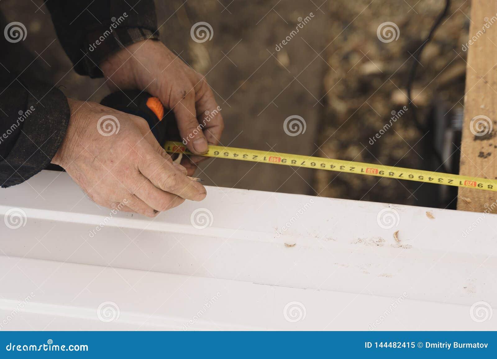 O construtor nas luvas mede o comprimento de um perfil do metal com uma fita métrica