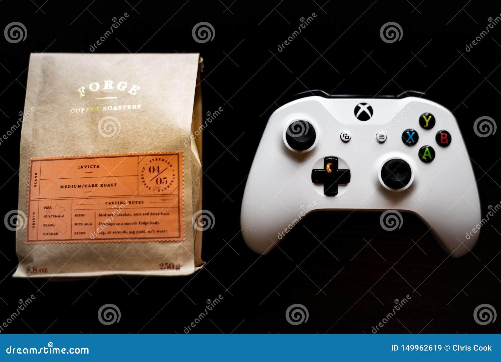 O controlador dos jogos do Xbox One sentou-se ao lado de um saco do café à terra contra um fundo preto escuro