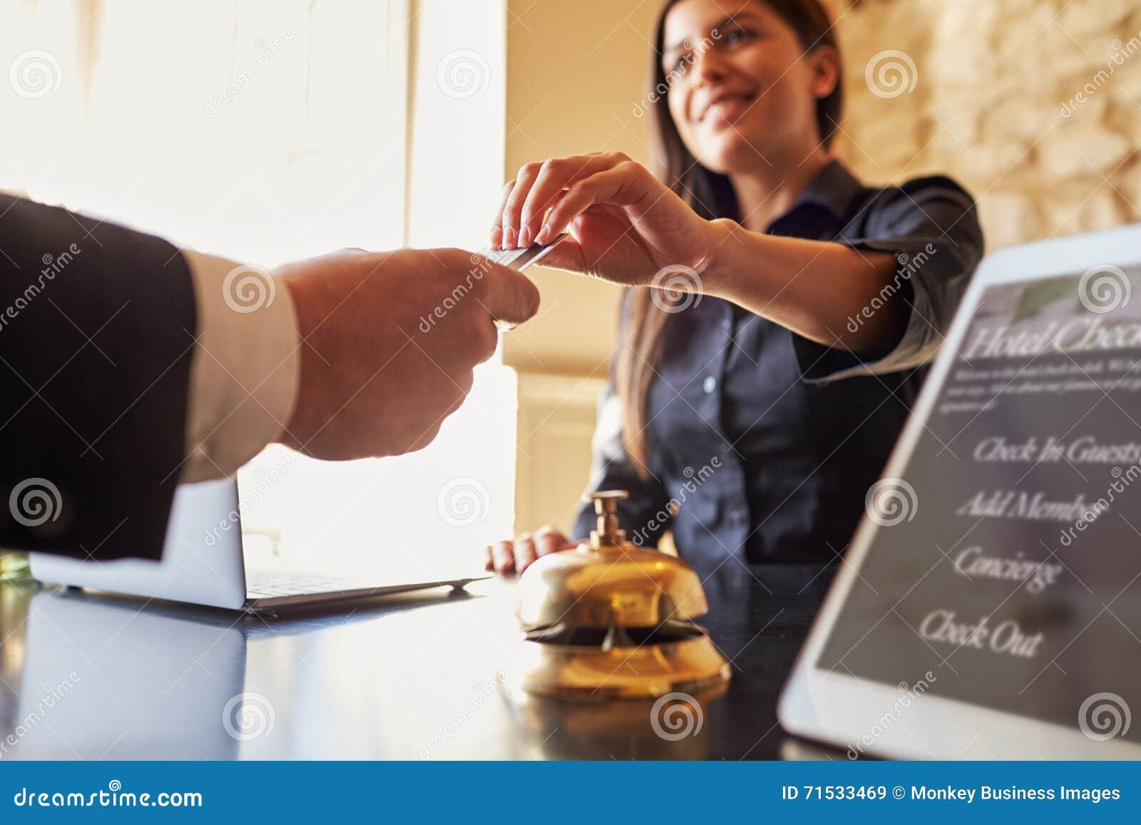 O convidado pega a sala o cartão chave na mesa de registro do hotel, fim