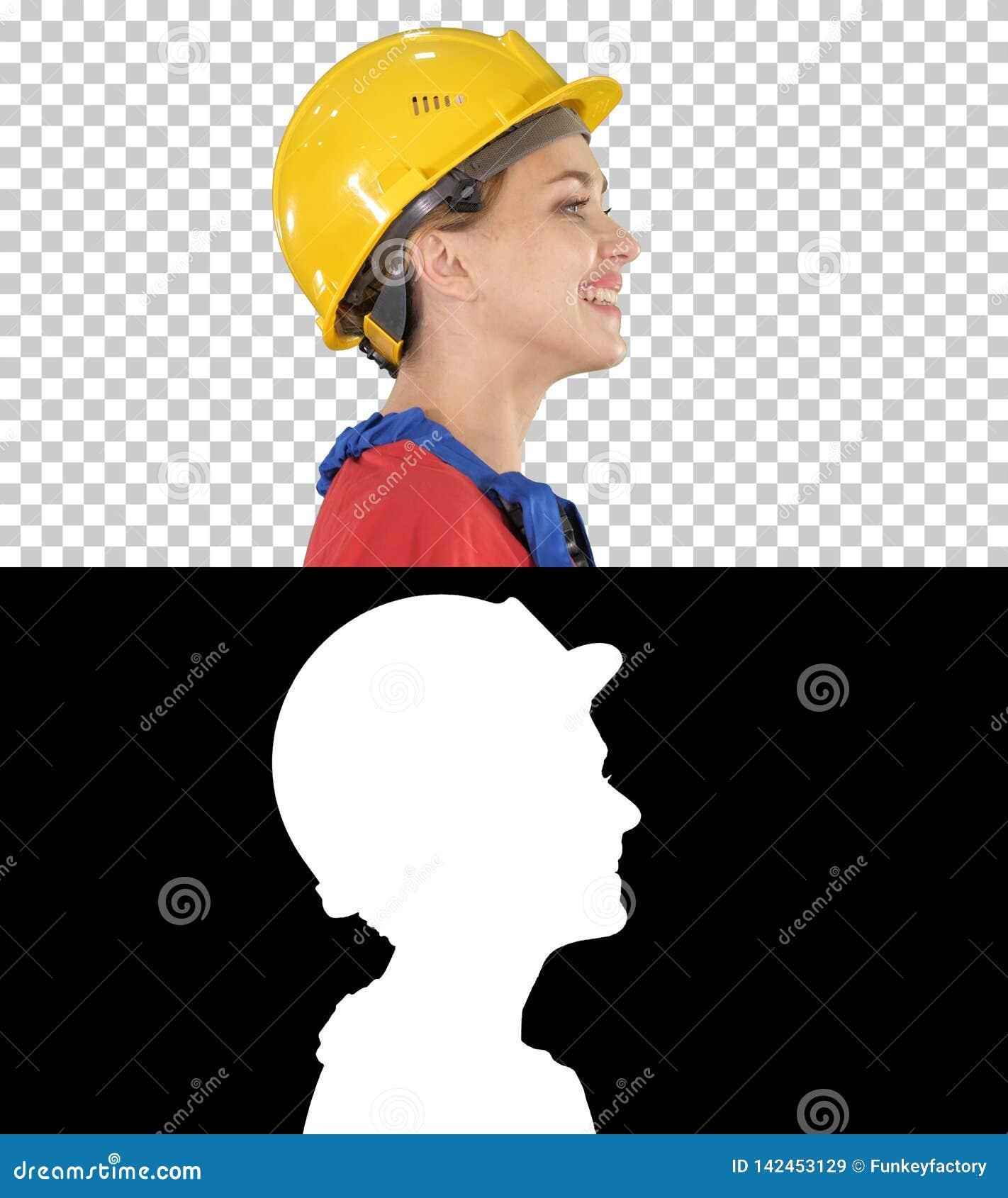 O coordenador da jovem mulher com o capacete de segurança amarelo que anda e que sorri, Alpha Channel