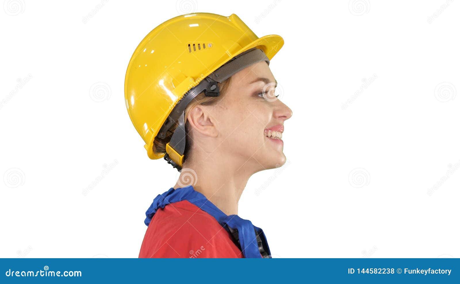 O coordenador da jovem mulher com o capacete de segurança amarelo que anda e que sorri no fundo branco