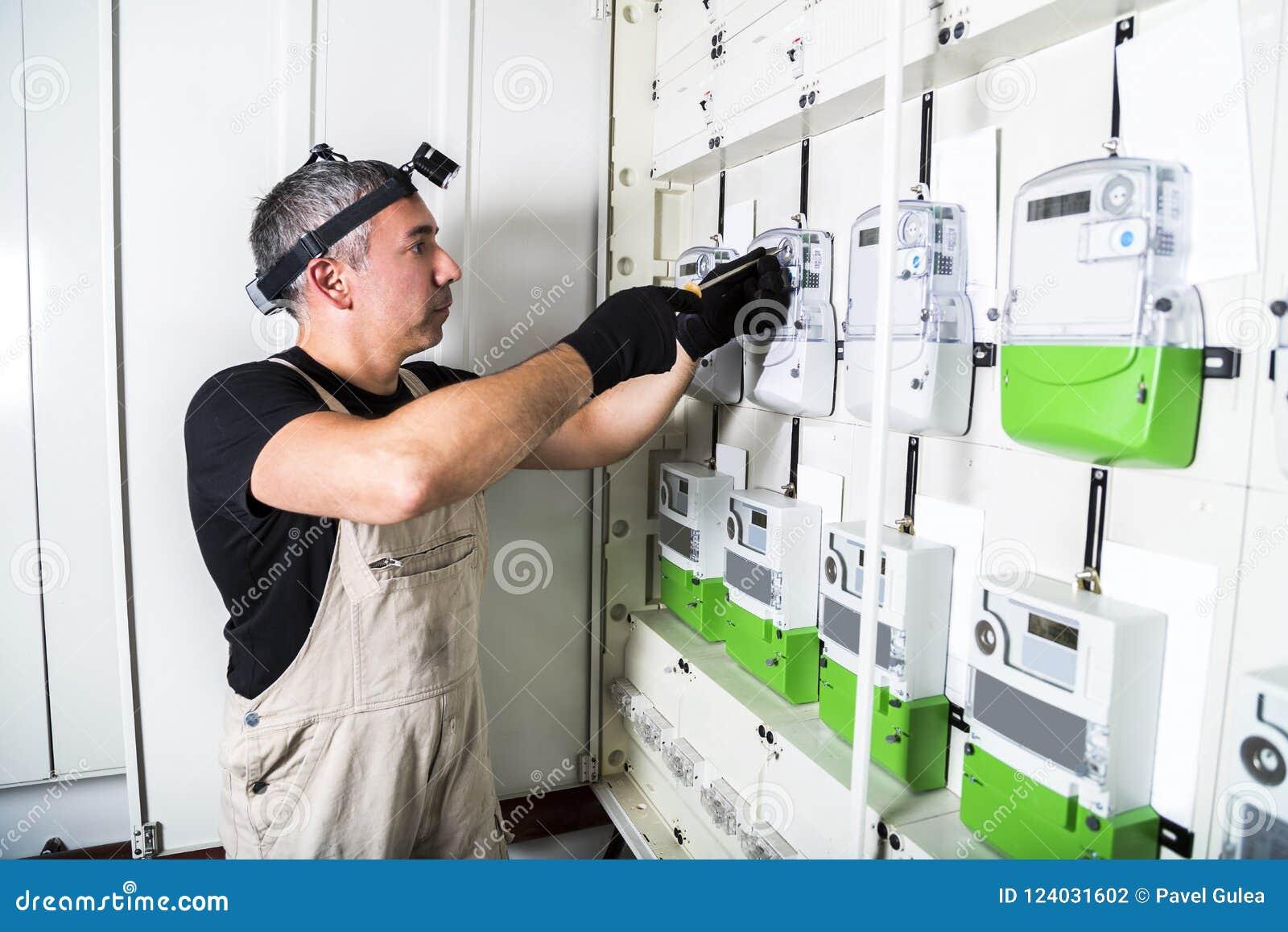O coordenador do eletricista trabalha com a chave de fenda na caixa de interruptor do fusível