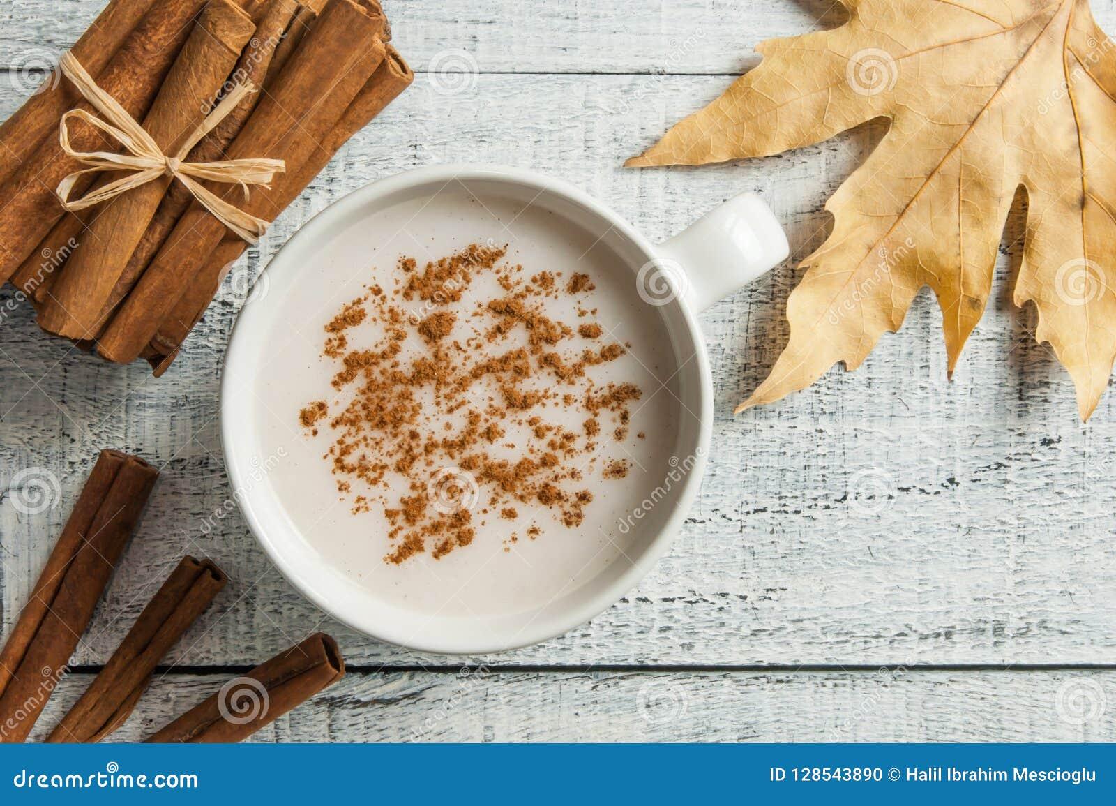 O copo branco da bebida quente leitosa do salep de Turquia com pó da canela e as varas inverno saudável da especiaria e do outono
