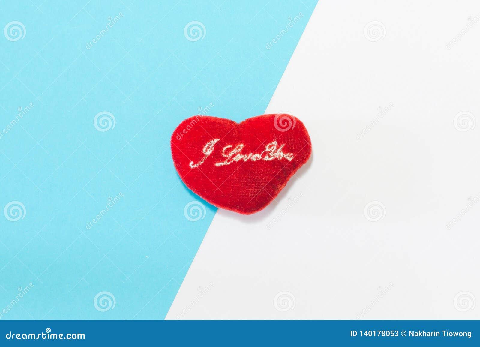 O coração é colocado no papel de duas cores com sobreposição azul e branca Conceito mínimo Fundo liso da configuração