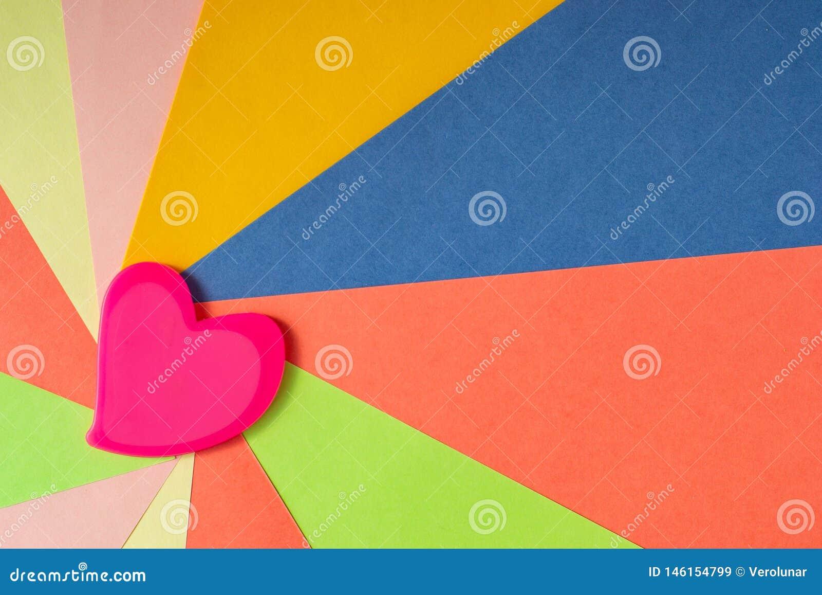 O cora??o cor-de-rosa no papel colorido sob a forma dos raios parte da borda esquerda