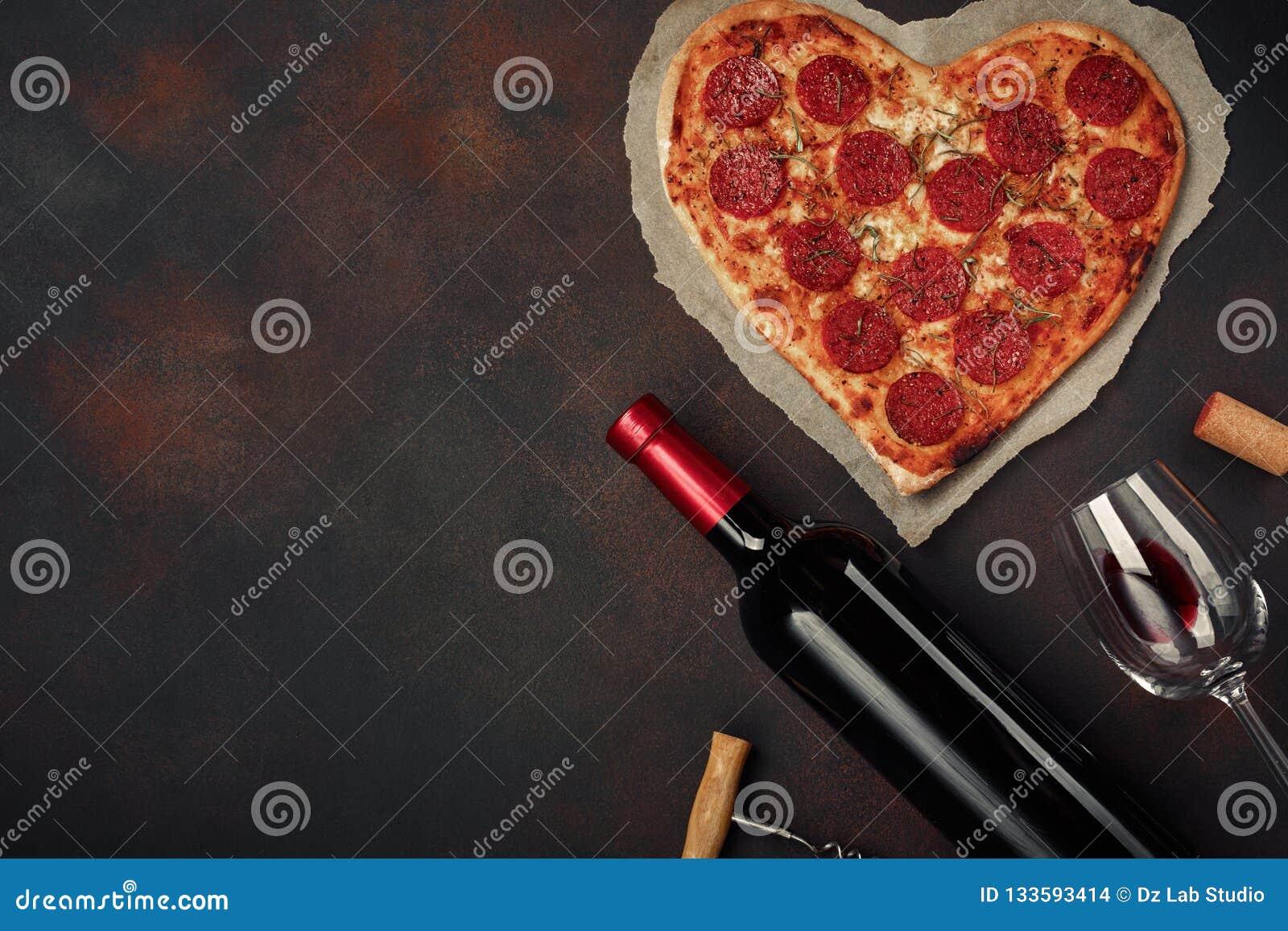 O coração deu forma à pizza com mussarela, sausagered com uma garrafa do vinho e dos wineglas no fundo oxidado