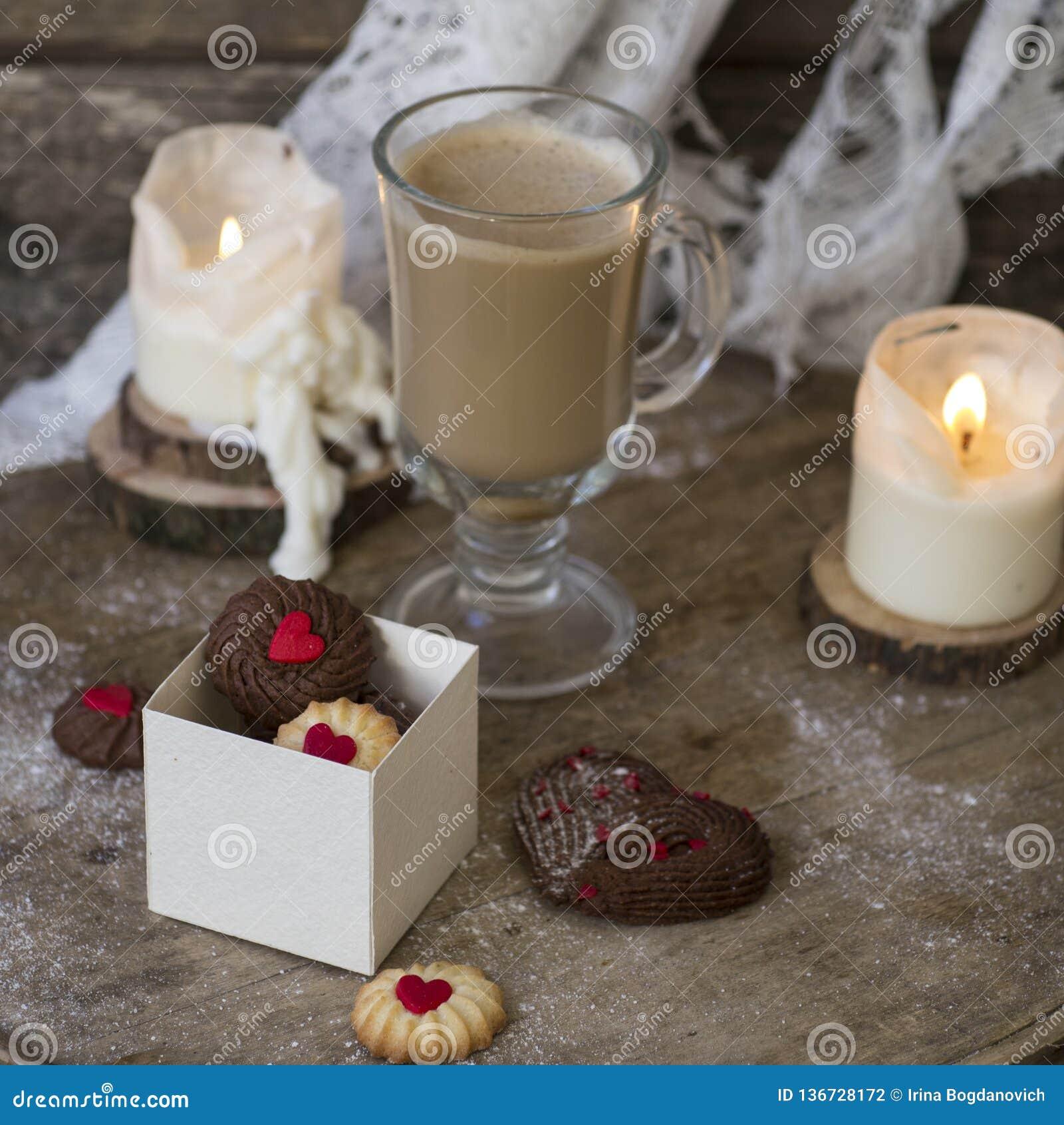 O coração deu forma a cookies vienenses do dia de Valentim do chocolate e da baunilha com uma xícara de café de vidro com leite e