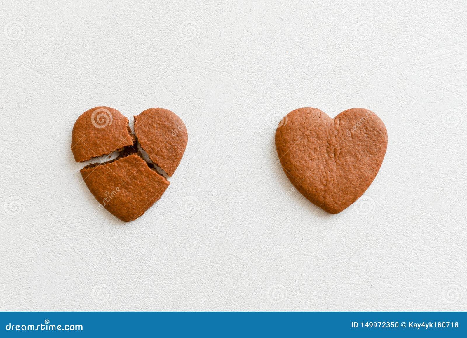 O coração dois deu forma às cookies, um delas é quebrado em um fundo branco A quebra coração-deu forma a cookies como um conceito