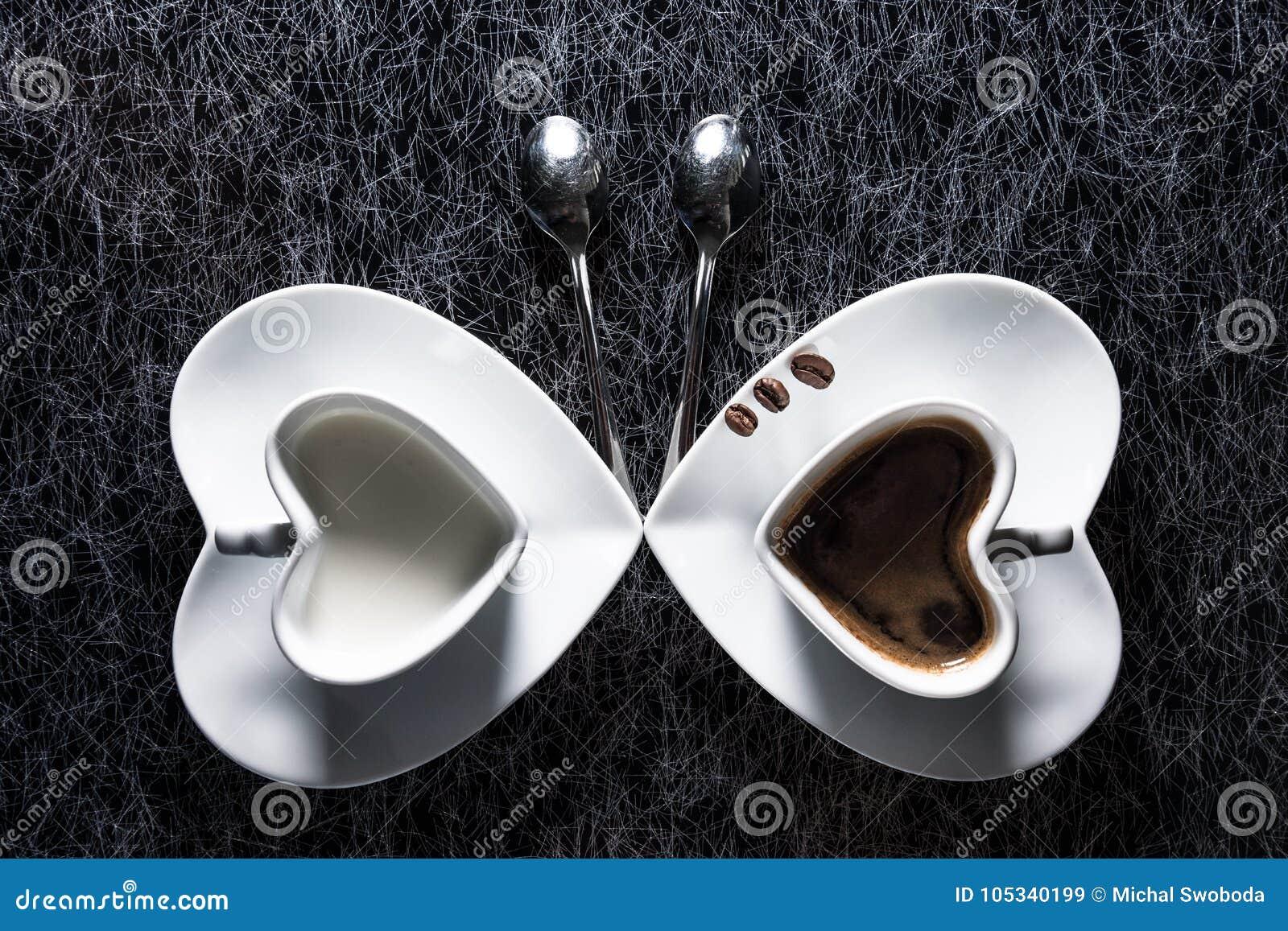 O coração dois deu forma a copos com café preto e leite que apontam entre si, com os três feijões de café