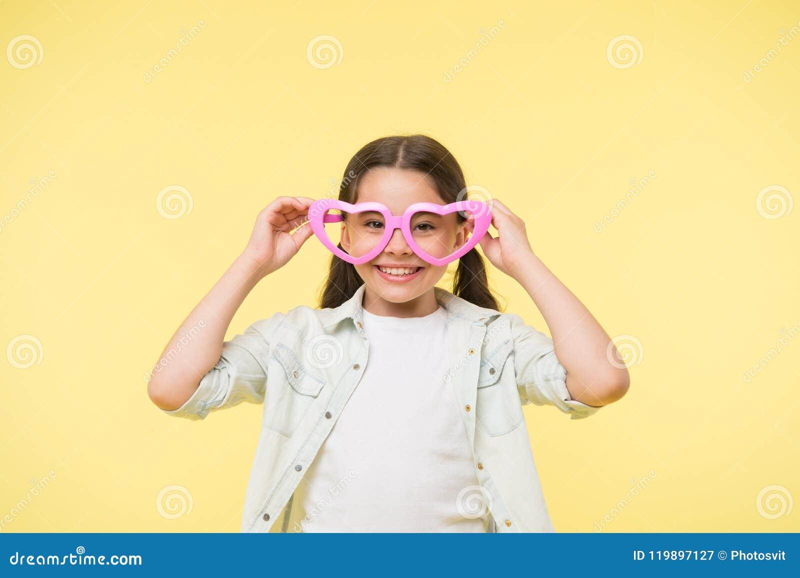O coração feliz do desgaste da criança deu forma a vidros no fundo amarelo Sorriso da menina no acessório de forma Olhar da forma