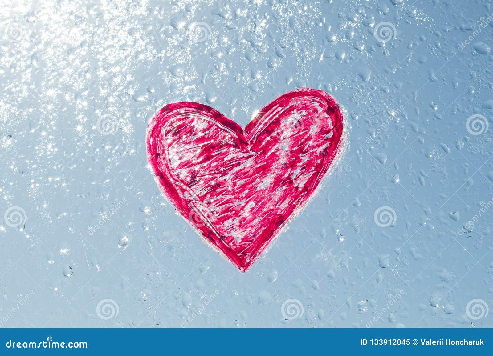 O coração vermelho pintado com batom na janela com água deixa cair O céu ensolarado azul do fundo, gotas brilha no sol