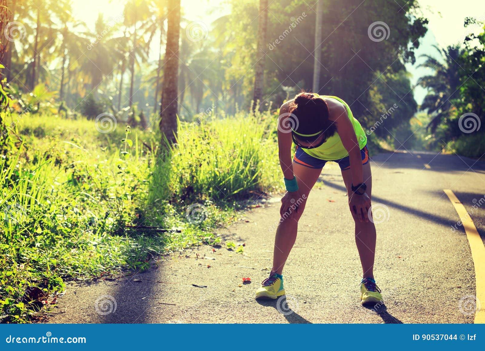 O corredor da mulher da aptidão toma uma ruptura na fuga tropical da floresta da manhã