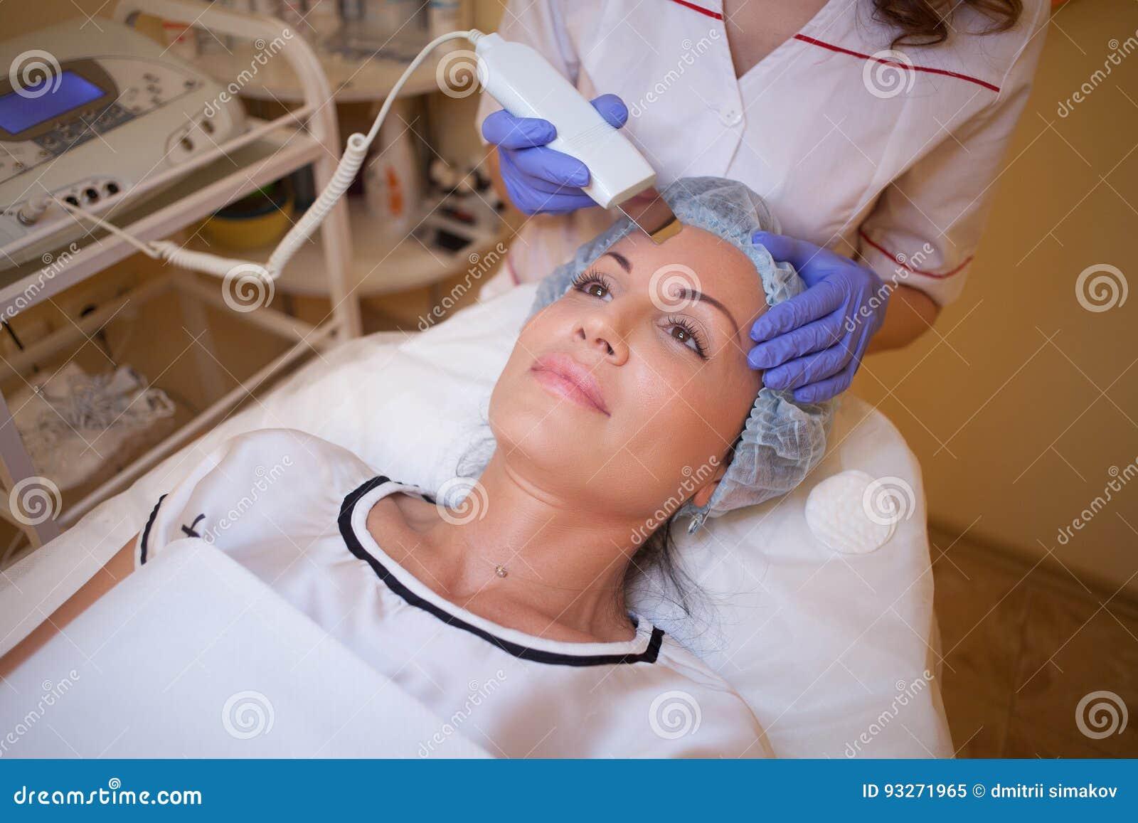 O cosmetologist do doutor faz ao procedimento uma mulher na cara dos termas