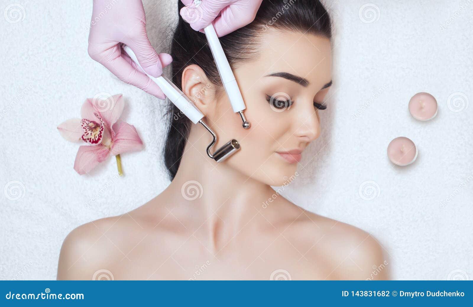 O cosmetologist faz ao instrumento um procedimento da terapia de um bonito, jovem mulher de Microcurrent em um salão de beleza