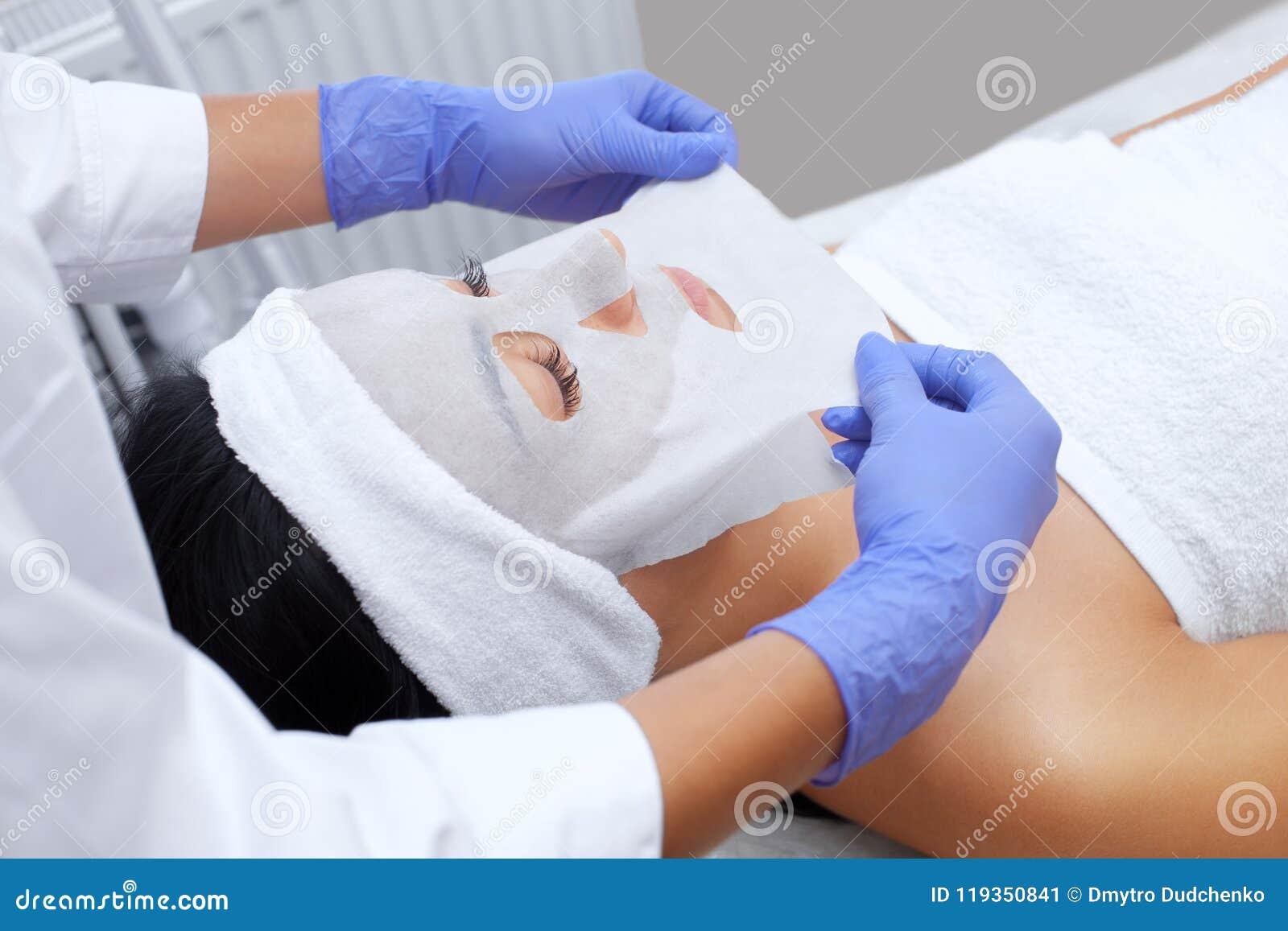 O cosmetologist para o procedimento de limpar e de hidratar a pele, aplicando uma máscara da folha à cara de uma jovem mulher no