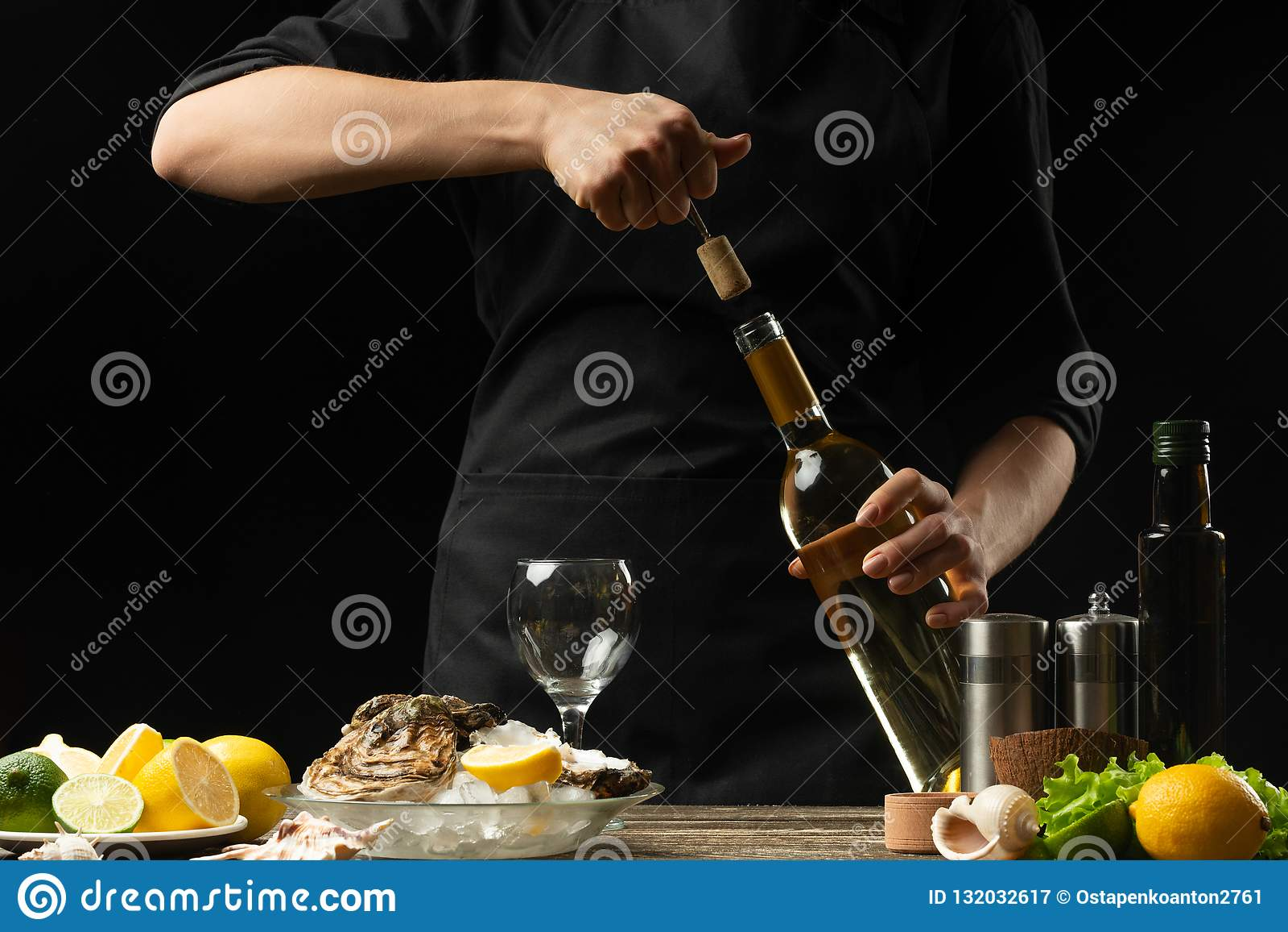 O cozinheiro chefe abre o vinho seco italiano com as ostras com limão, em um fundo escuro