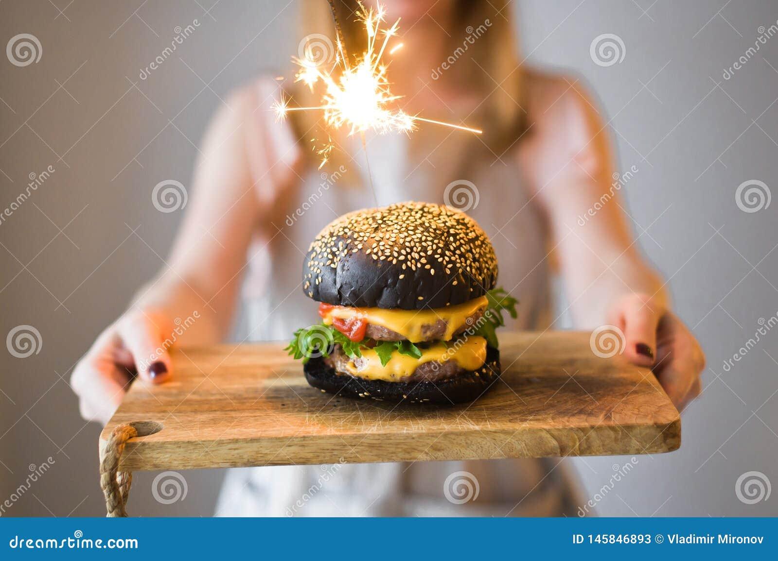 O cozinheiro chefe da menina realiza em suas m?os uma placa de corte de madeira com cheesburgers pretos