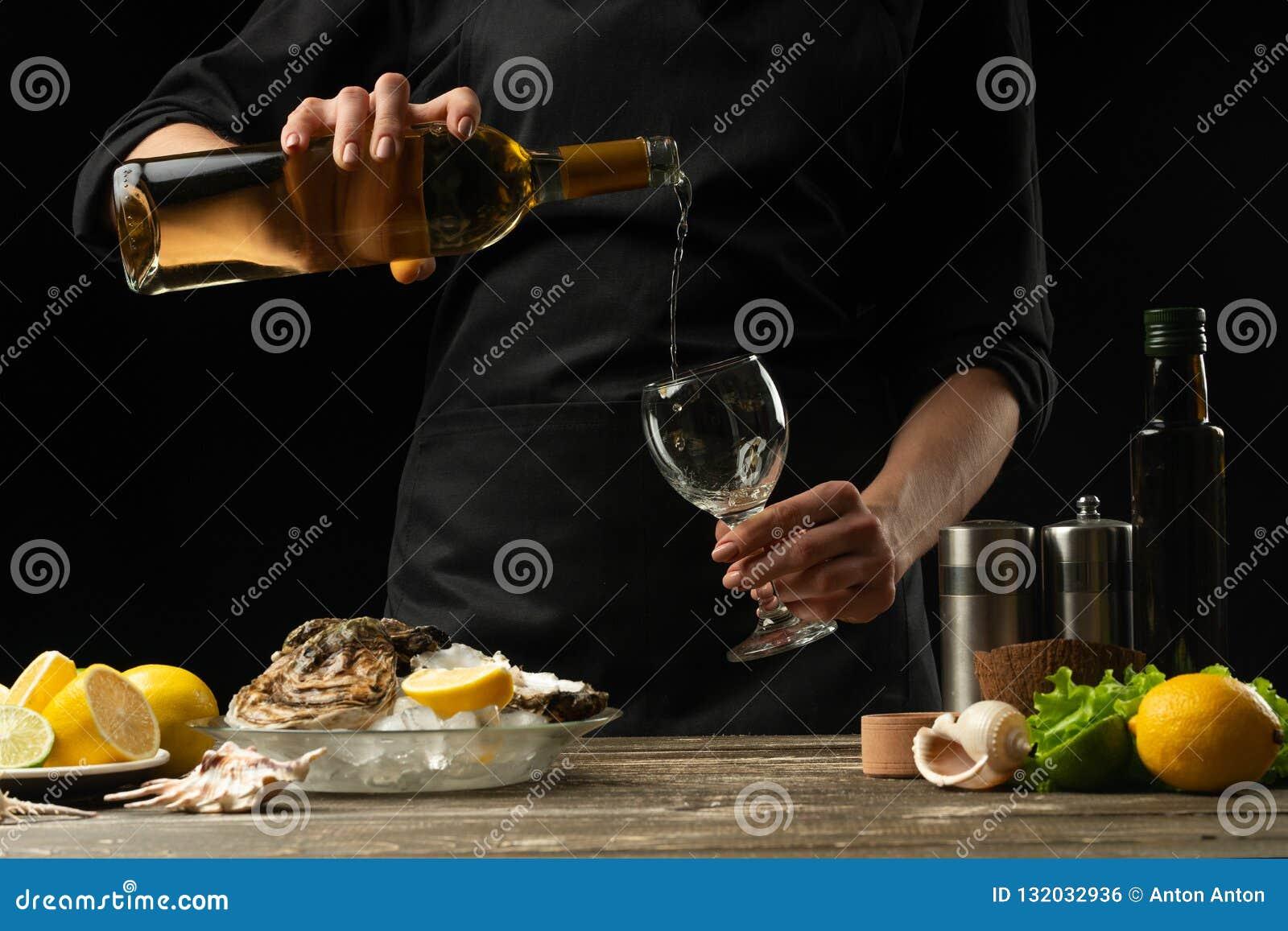 O cozinheiro chefe derrama, prova o vinho seco italiano da ostra com limão