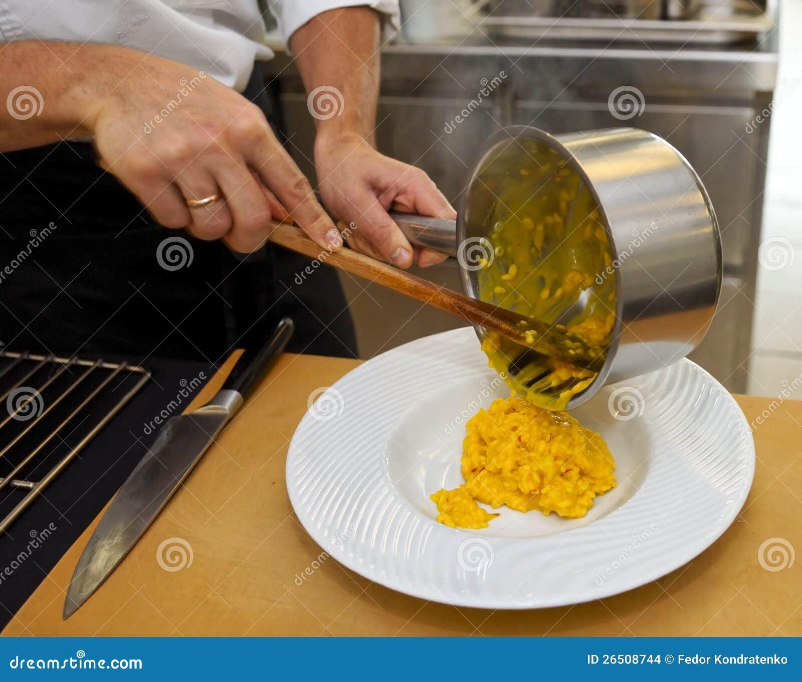 O cozinheiro chefe está derramando o risotto na placa