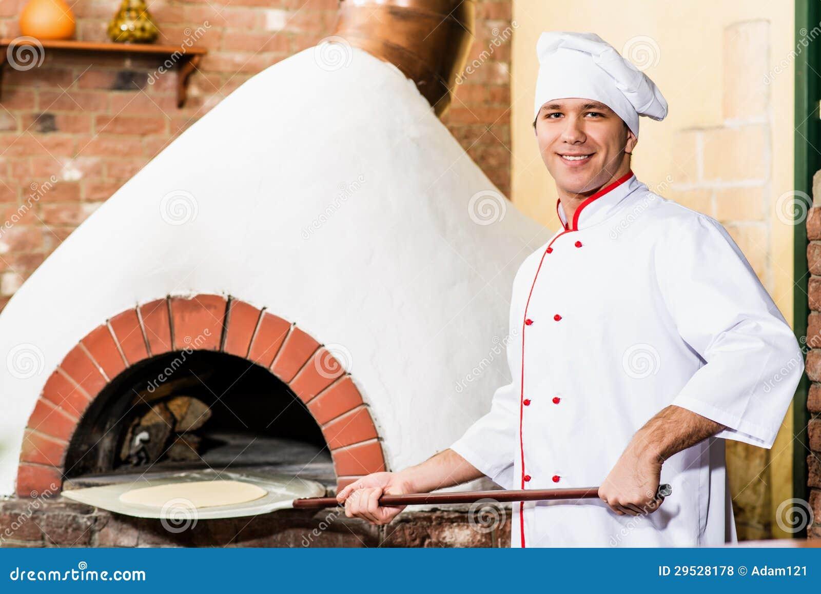 O cozinheiro chefe põe a massa no forno para pizzas,