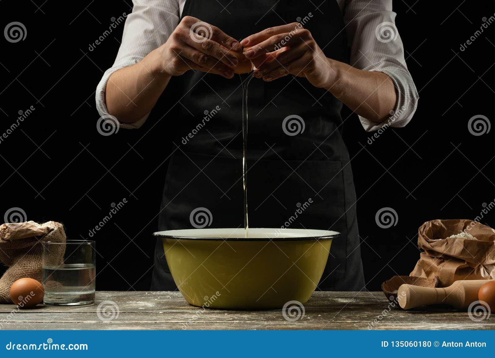 O cozinheiro chefe trabalha com massa, quebra o ovo e os chicotes, para a preparação do focaccia, da massa italiana, da pizza ou