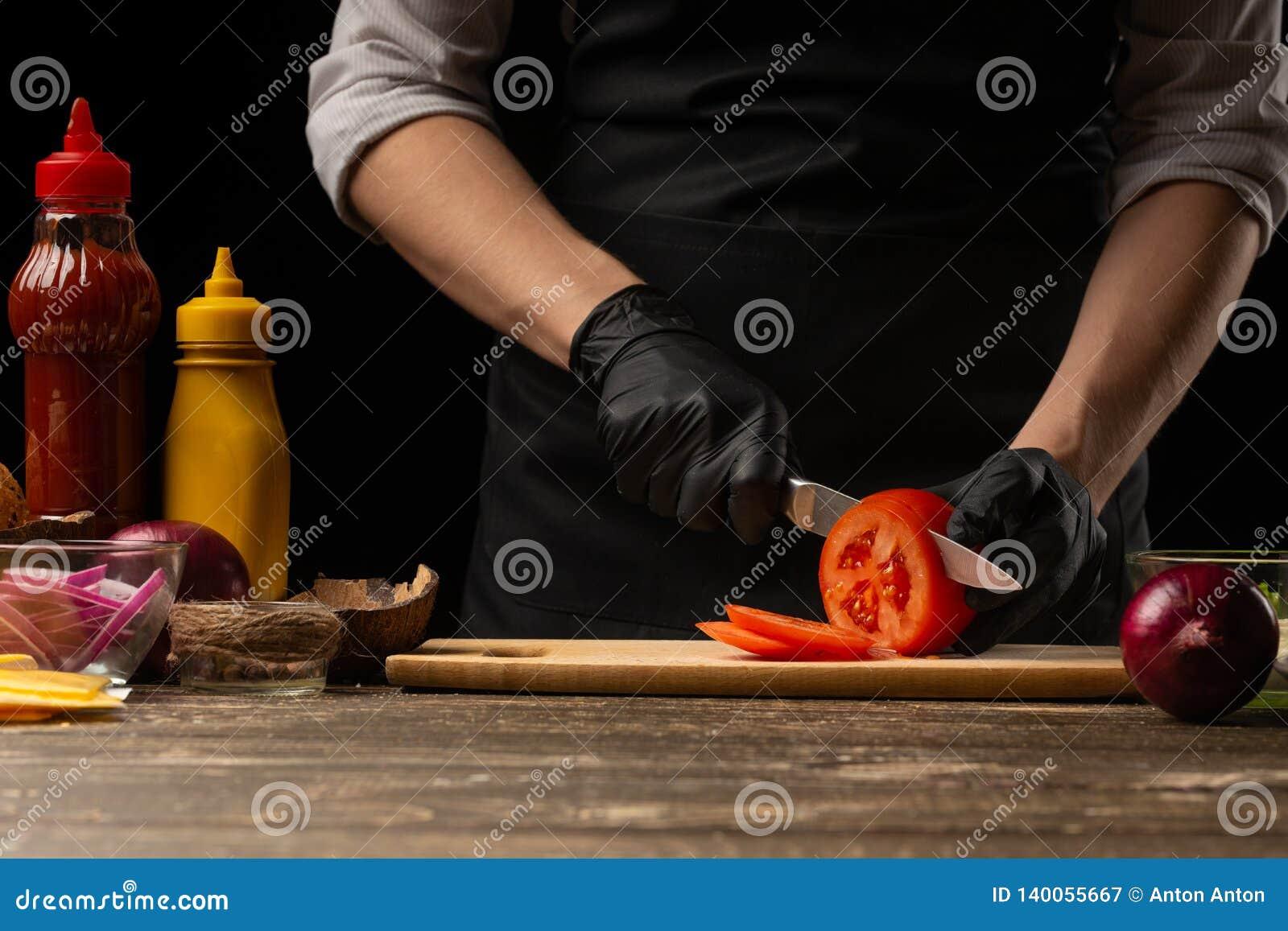 O cozinheiro corta um tomate fresco para fazer um hamburguer, um Hamburger Em um fundo com ingredientes Delicioso e fast food, fa