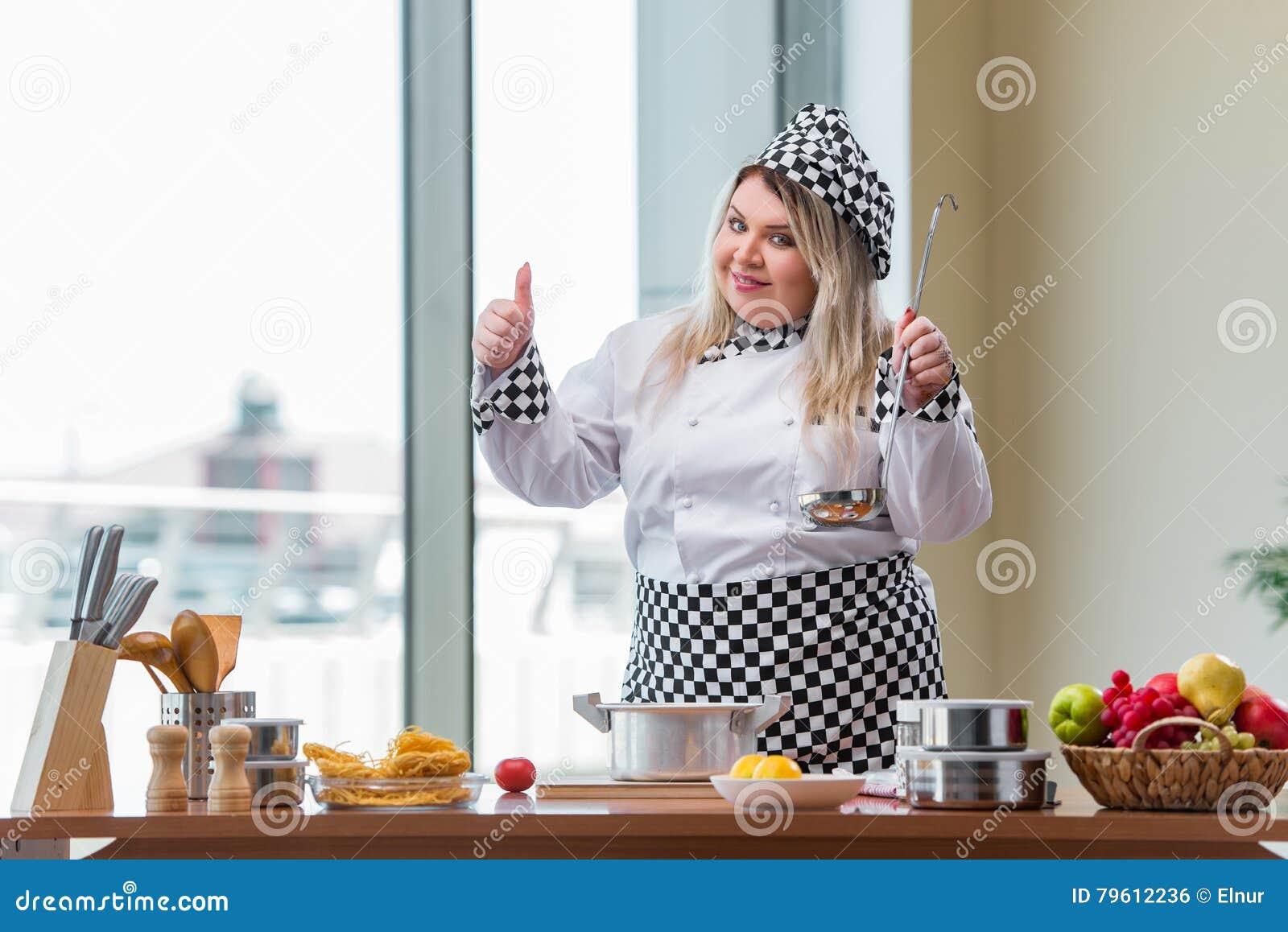 O cozinheiro da mulher que trabalha na cozinha brilhante